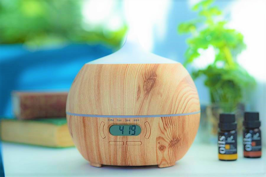 bluetooth-alarm-clock-oil-diffusers-on-table-with-plants-books-and-essential-oils