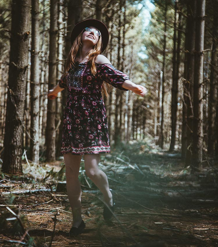 free spirited woman twirling on forest trail