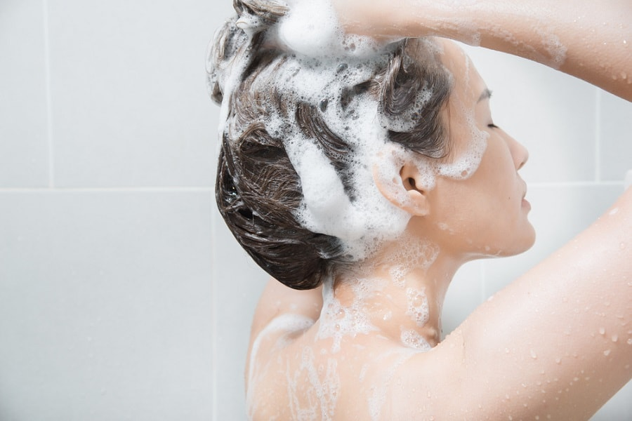 woman-in-shower-uses-shampoo-with-lemon-oil-for-greasy-hair