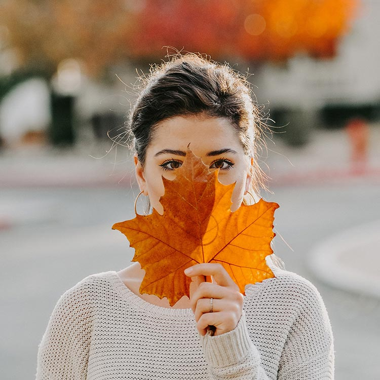 woman covering face with bright orange autumn leaf