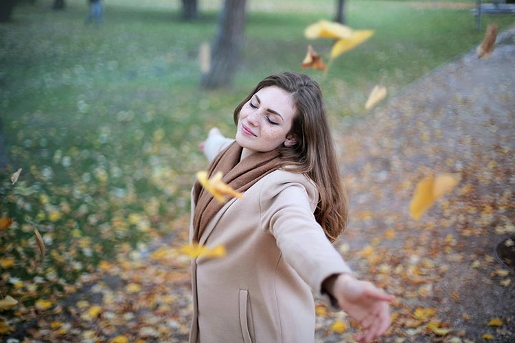 woman twirling while autumn leaves fall in park